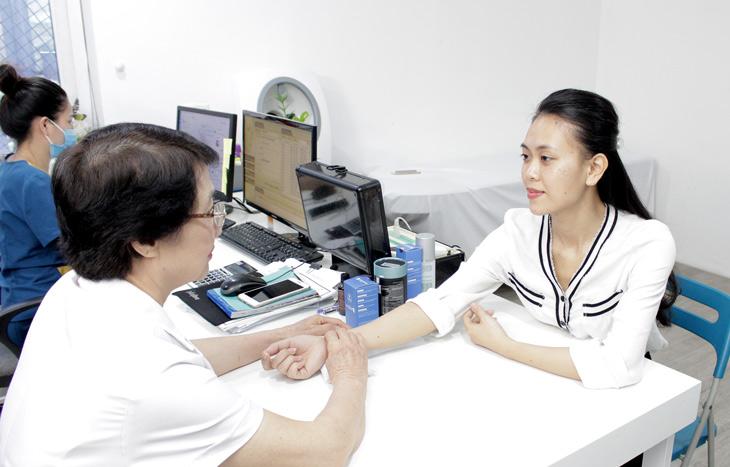 Bác sĩ Nhuần thăm khám và bắt mạch cho chị Trang